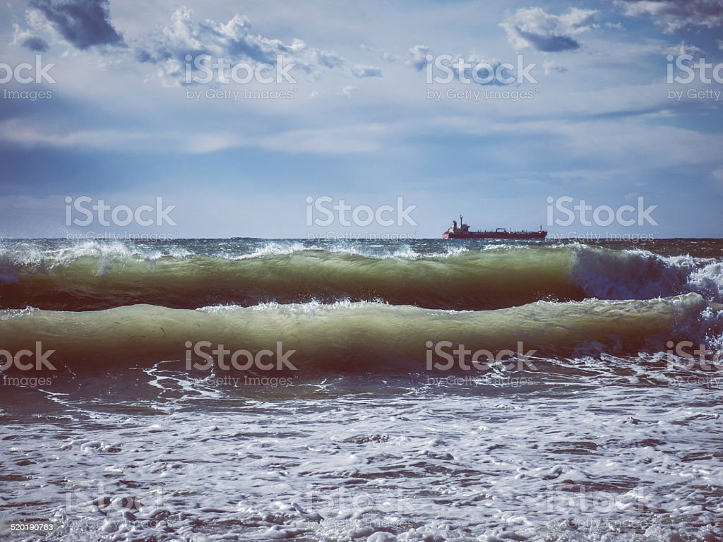 Lonely ship in stormy rough sea stock photo