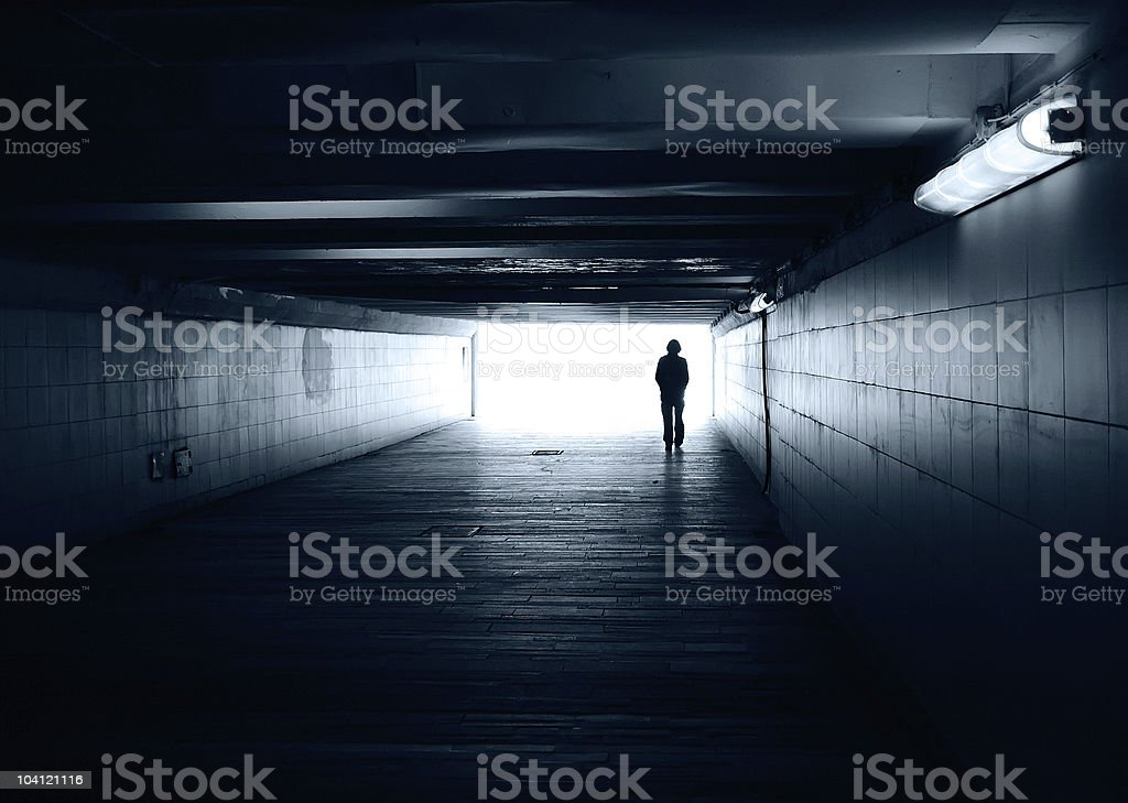 Lonely silhouette in a subway tunnel stock photo
