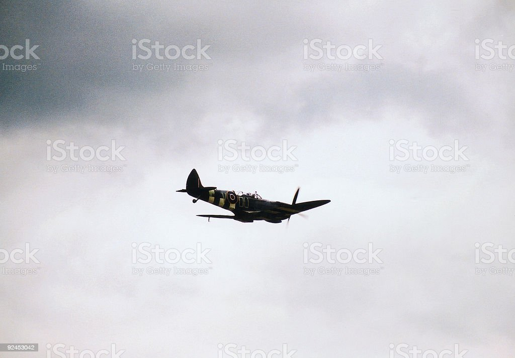 Lonely spitfire cruises under a dark sky stock photo