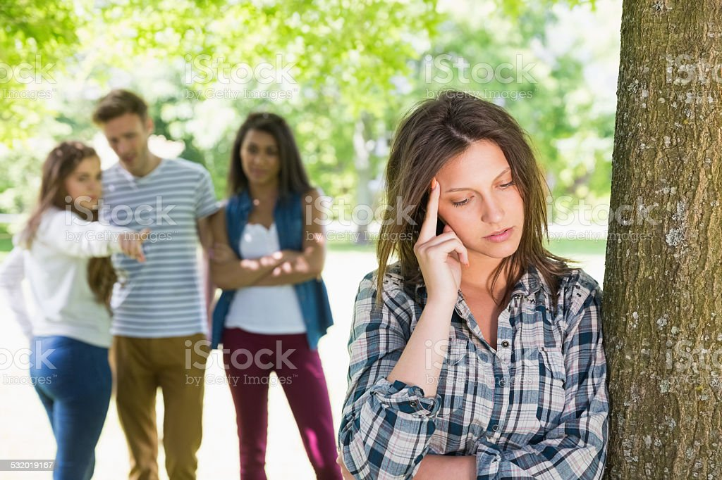 Lonely student being bullied by her peers stock photo