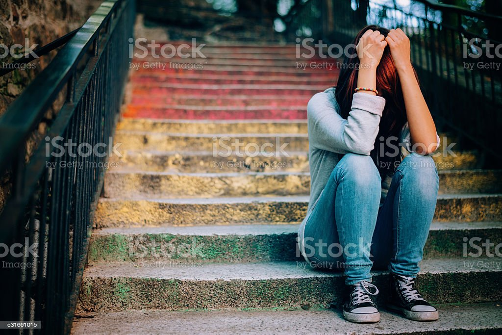 Lonely teenager crying outdoors stock photo