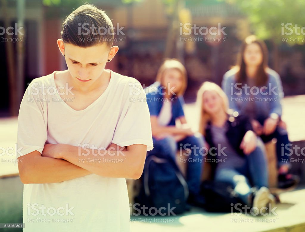 Lonely teenager standing away stock photo