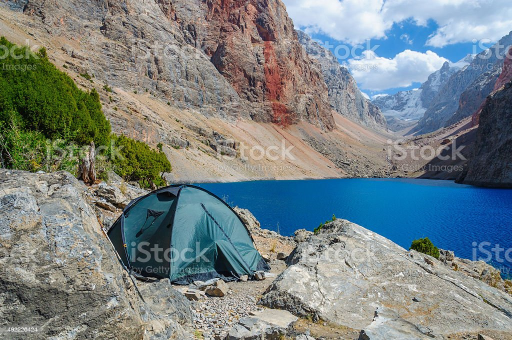 Lonely tent stands on the shore of a mountain lake stock photo