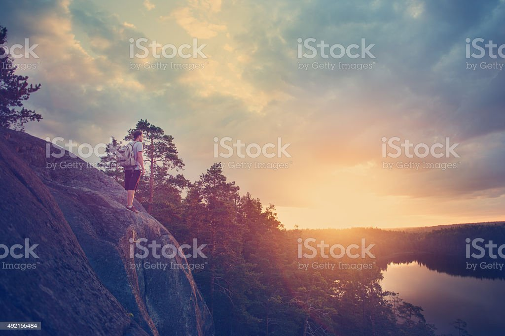 Lonely traveler with backpack looking at sunset stock photo