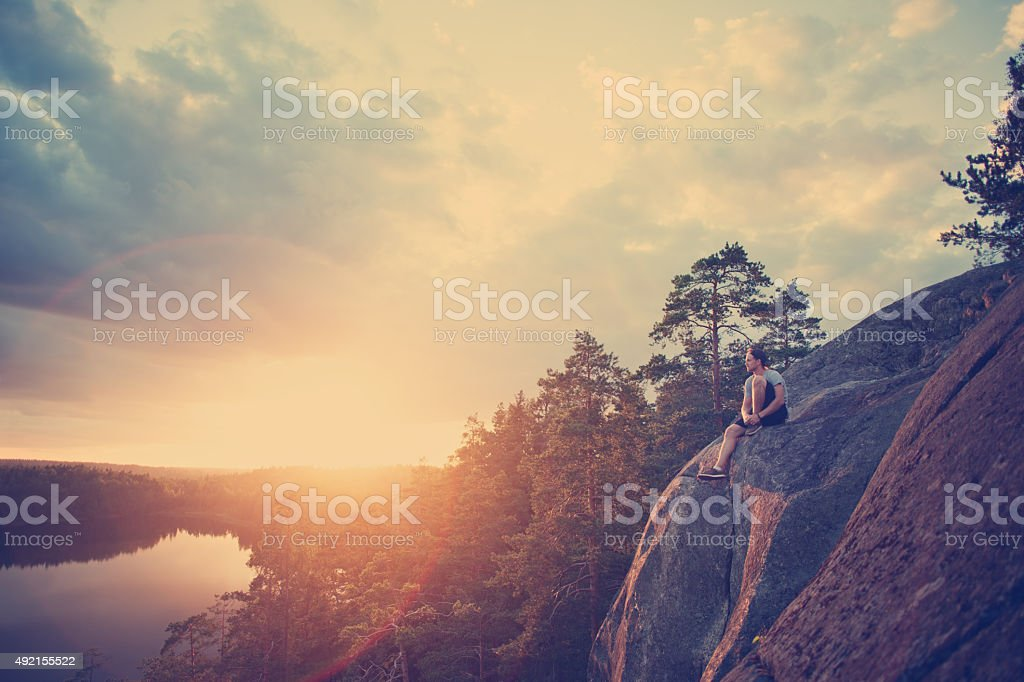 Lonely traveler with backpack sitting and looking at sunset stock photo