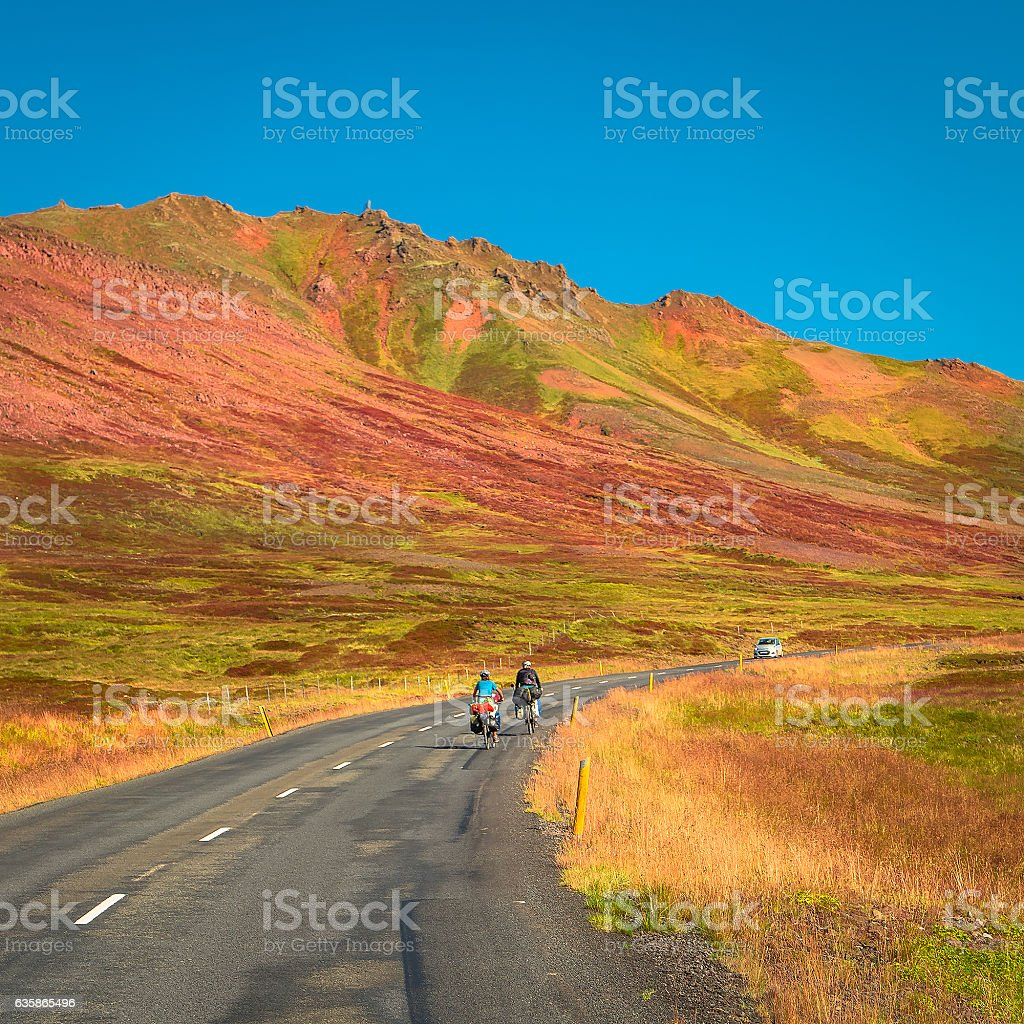 Lonely two travellers with bikes on Icelandic road, summer stock photo