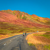 Lonely two travellers with bikes on Icelandic road, summer