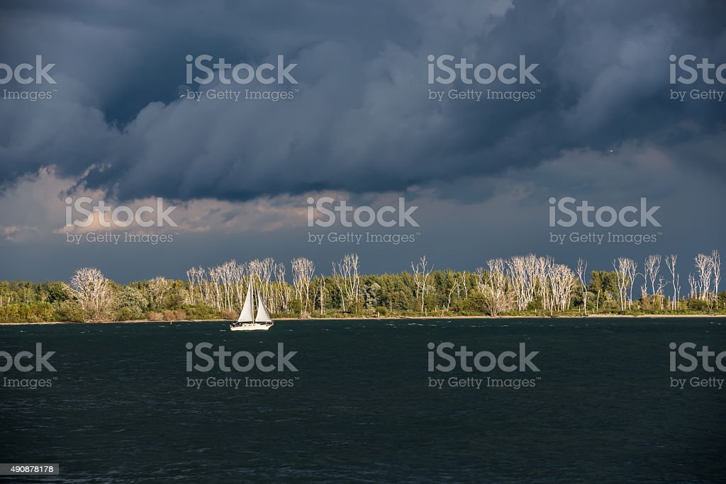 Lonely white sailing boat between dark water and depressing clouds stock photo
