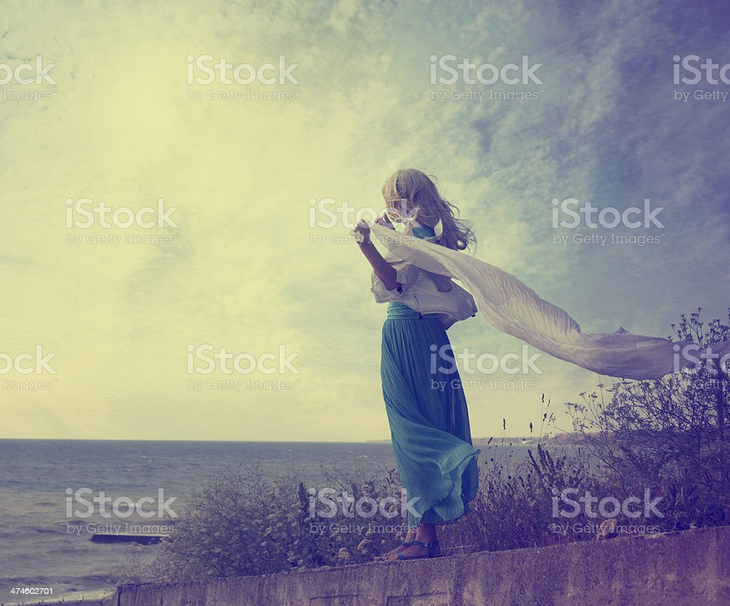 Lonely Woman in Turquoise Dress with Waving Scarf stock photo