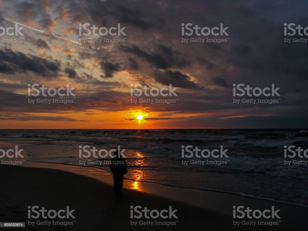 Lonely woman is walking along the sea coast towards sunset stock photo