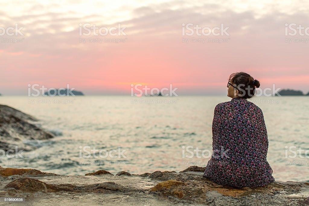 Lonely woman sitting on seashore after sundown. stock photo