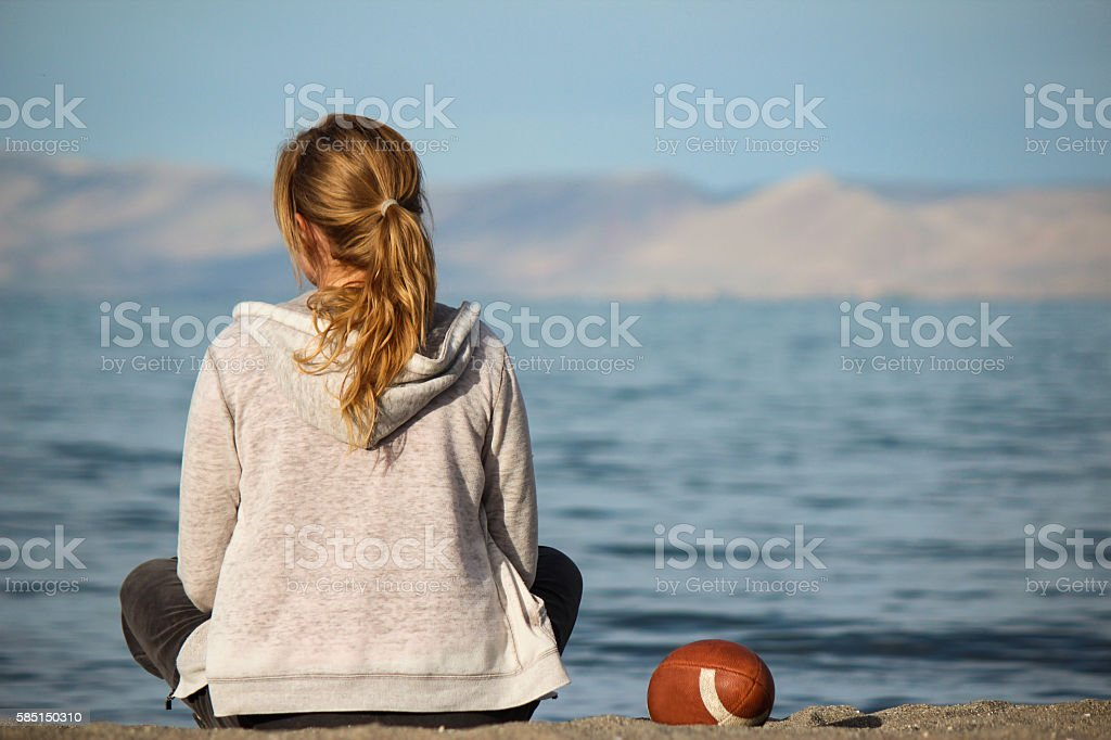 Lonely Woman Sitting on the Beach stock photo