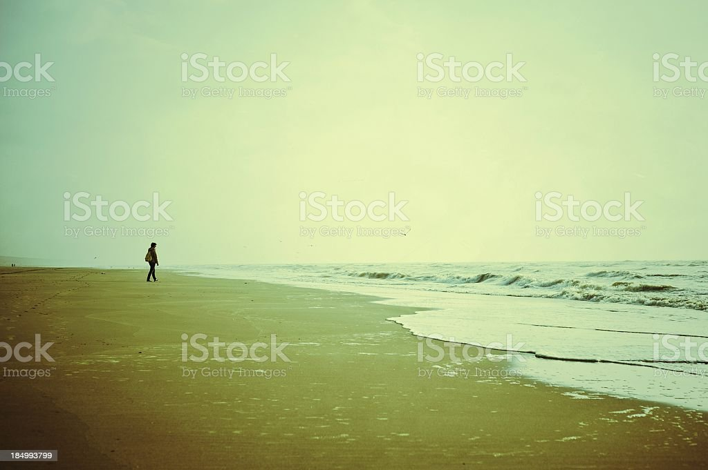 Lonely Woman Walking On The Seashore At Sunset royalty-free stock photo