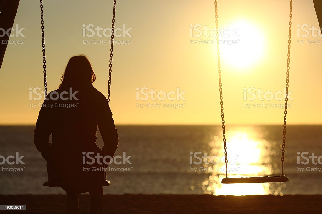 Lonely woman watching sunset alone in winter stock photo