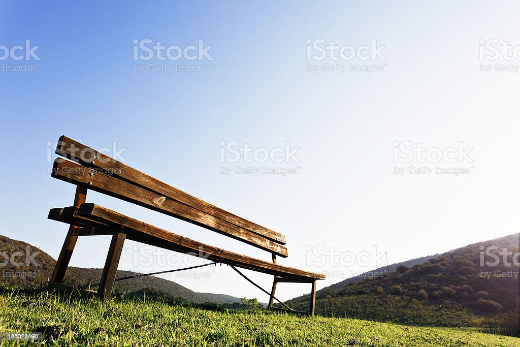 Lonely wooden bench on deserted grassy hill royalty-free stock photo