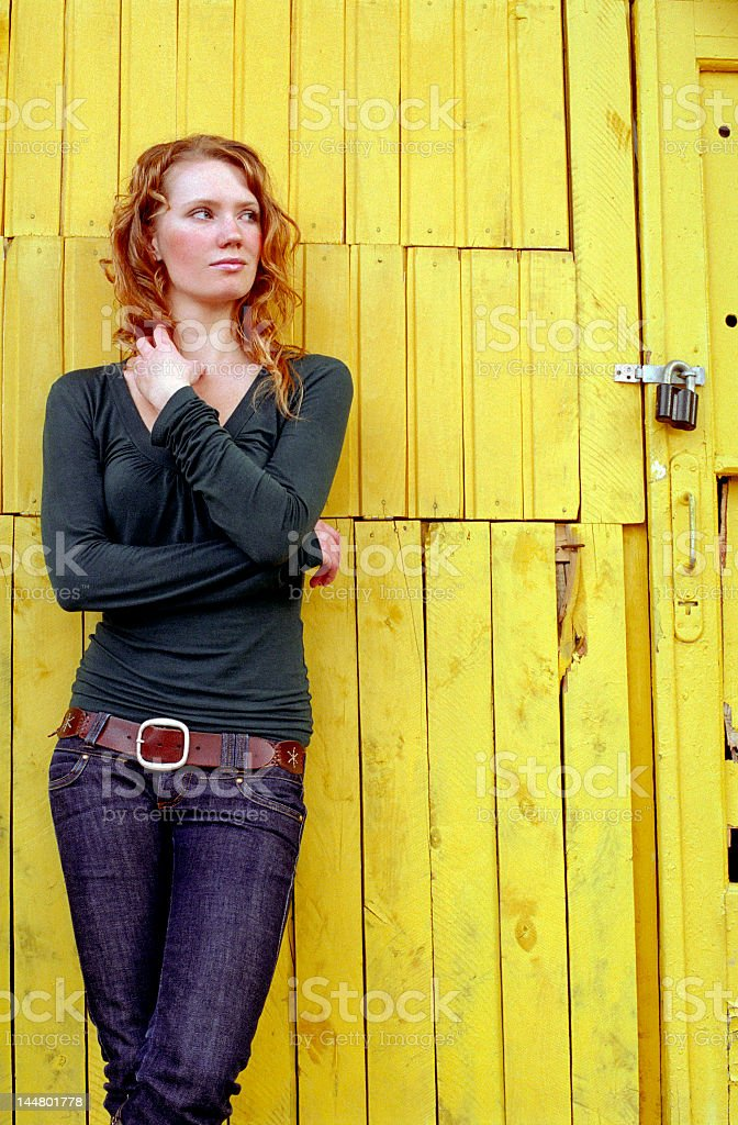 lonely young woman before a yellow wall royalty-free stock photo