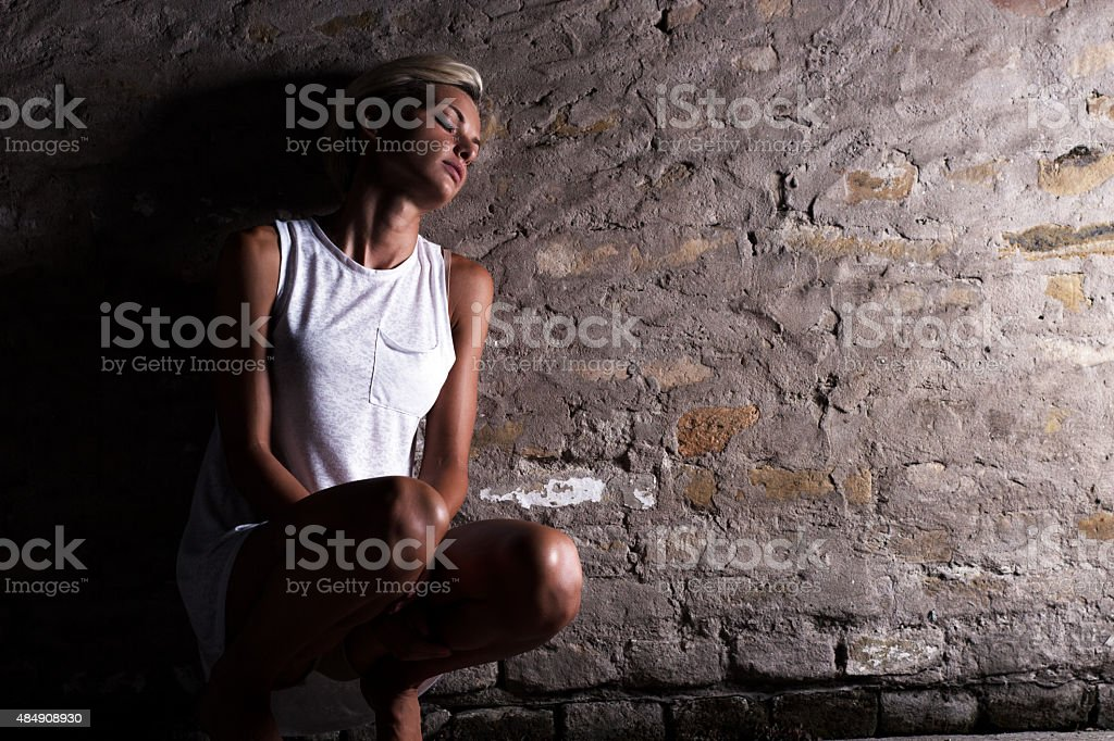 Lonely young woman sitting on the street stock photo