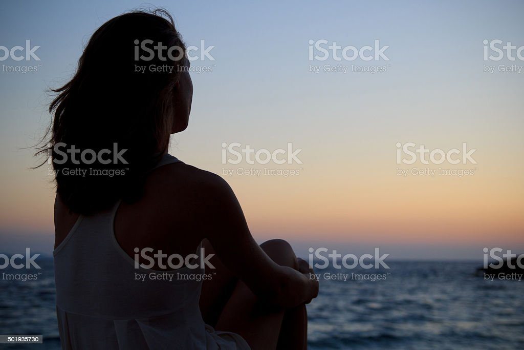 Lonely young woman, watching the sea sunset stock photo
