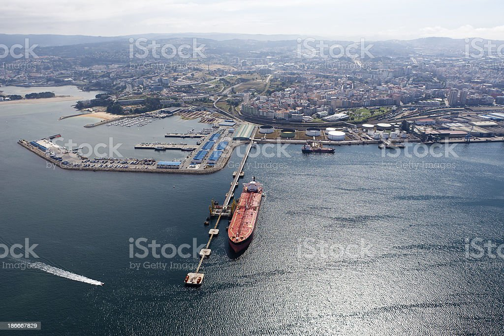 Long aerial view of oil tanker in port with city behind stock photo