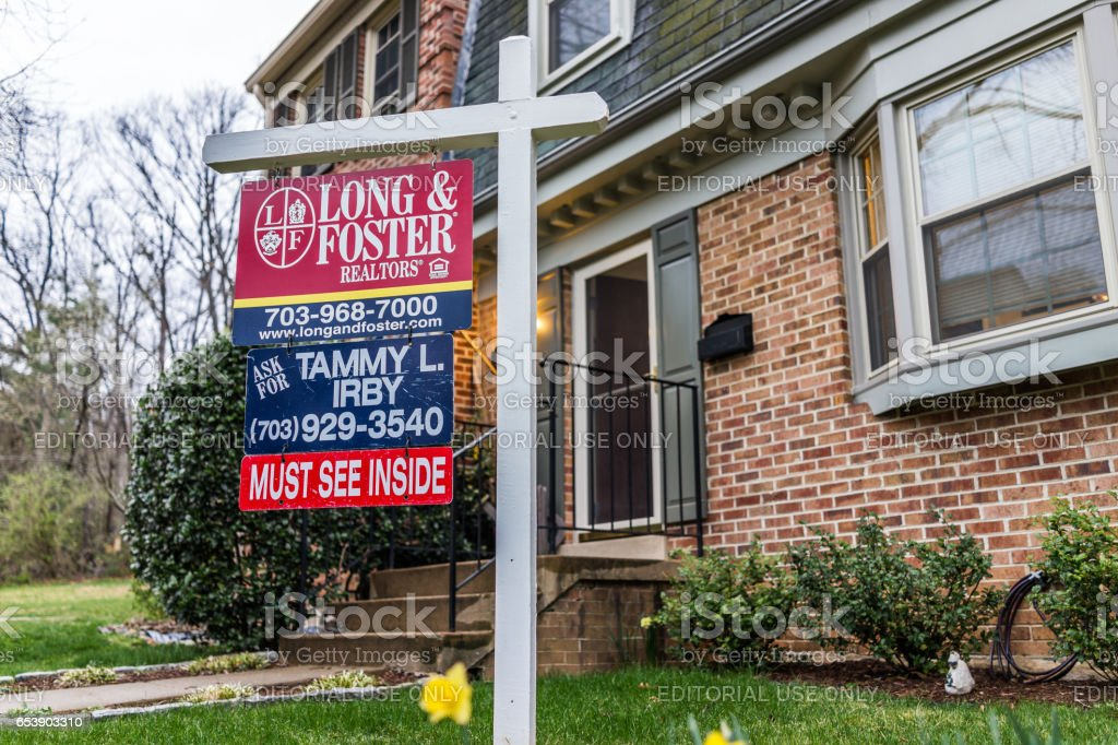 Long and Foster real estate sign in front of townhouse with yellow daffodils stock photo