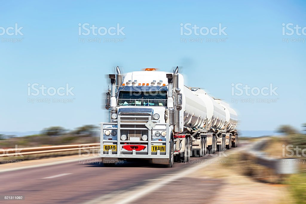 Long and heavy fuel road-train crossing bridge at speed stock photo
