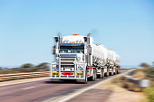 Long and heavy fuel road-train crossing bridge at speed