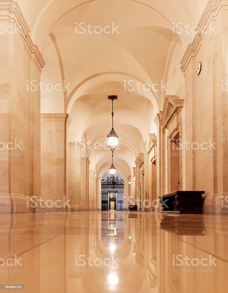 Long arched hallway with a wrought iron gate at one end royalty-free stock photo