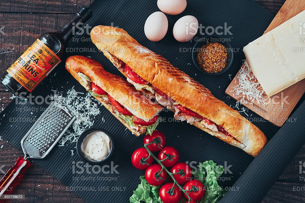 long baguette sandwich with lettuce on black background stock photo