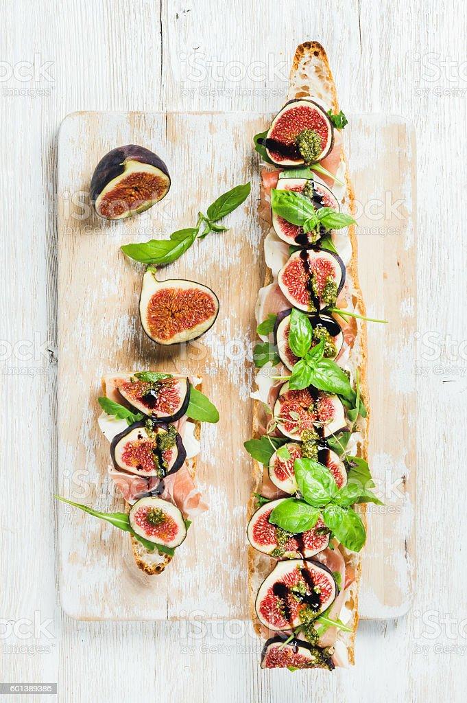 Long baguette sandwich with prosciutto, mozzarella, arugula, figs and basil stock photo