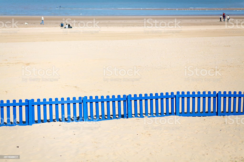 Long Blue Fence On The Beach. stock photo