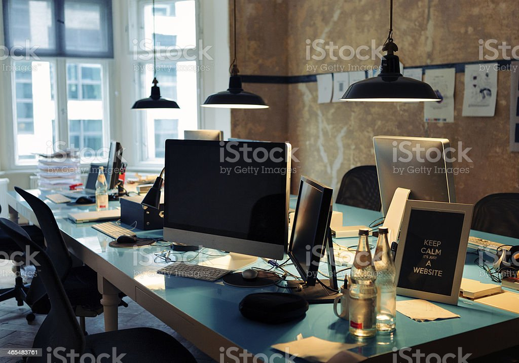 Long blue table covered in computers and papers royalty-free stock photo