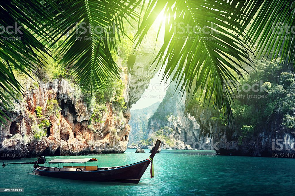 A long boat docked on beach in Krabi, Thailand summers stock photo