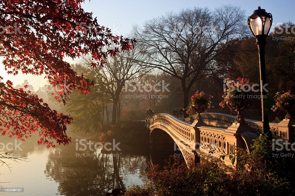 Long bow bridge over large river surrounded by trees stock photo