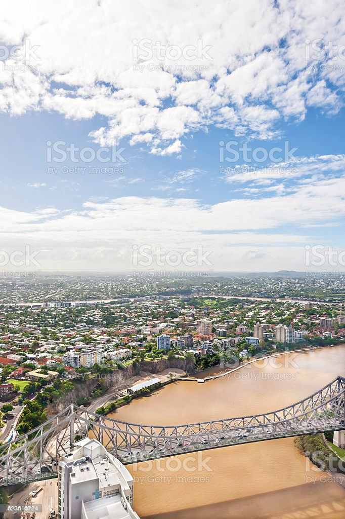 Long bridge on muddy water near city and sky. stock photo