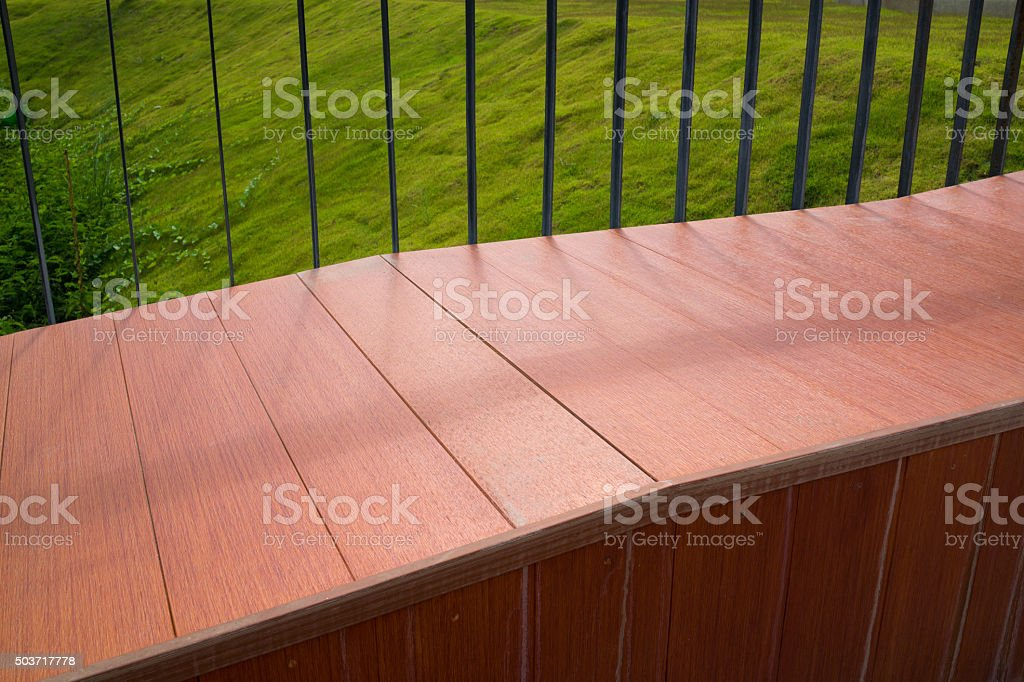 Brun Long banc en bois avec de l'herbe verte dans un arrière-plan photo libre de droits