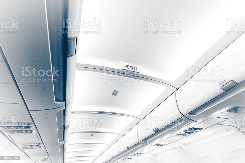 long ceiling in airplane with exit sign stock photo