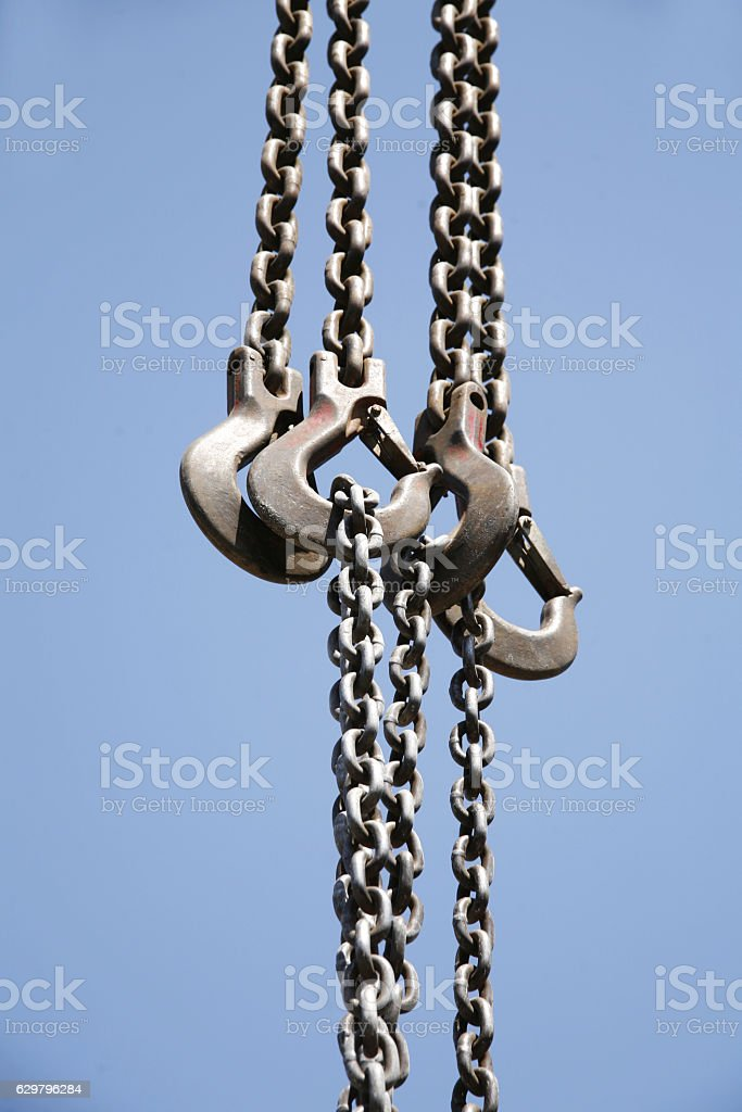 Long chains with hooks hanging vertically against blue sky stock photo