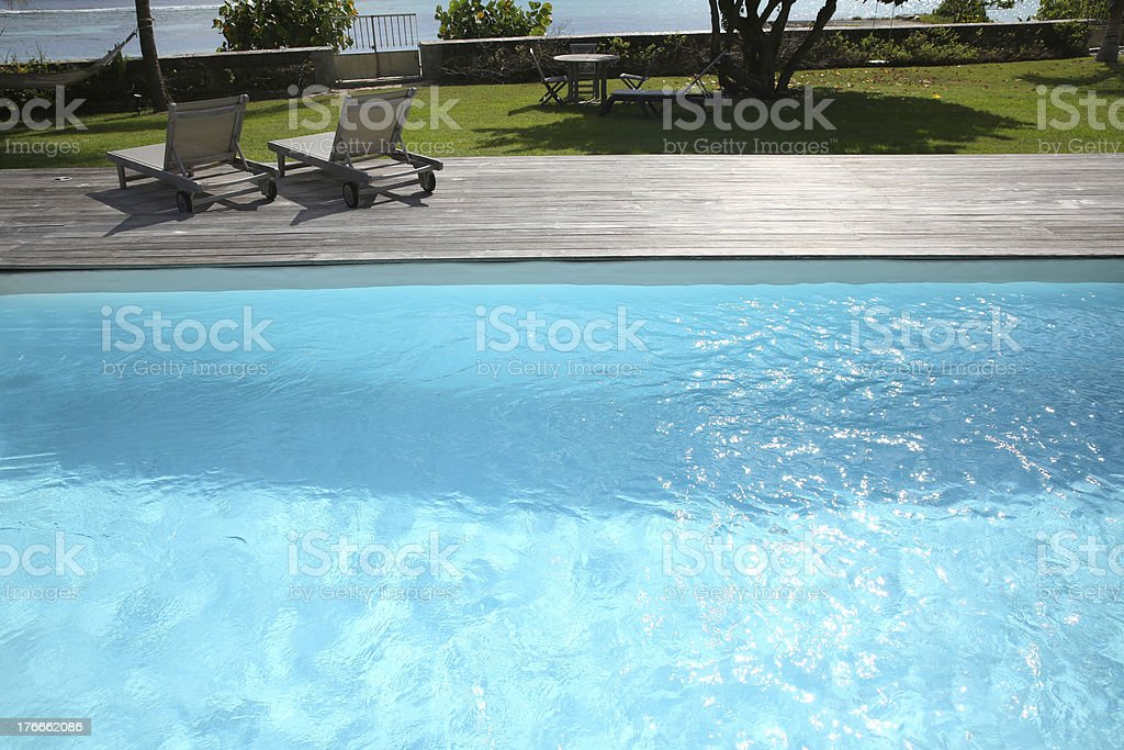 Long chairs on pool deck royalty-free stock photo