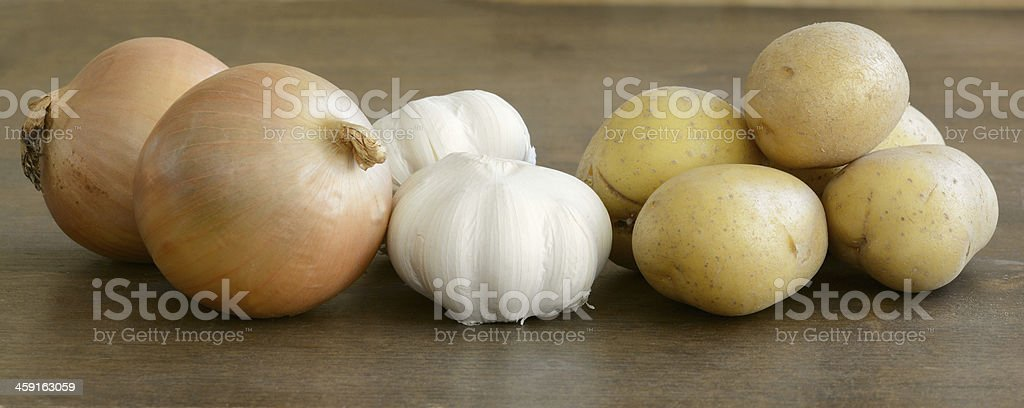 Long close up of fresh onions, garlic, and potatoes royalty-free stock photo