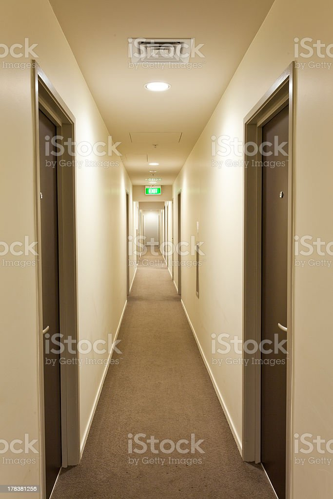 Long corridor with hotel room doors and exit sign stock photo