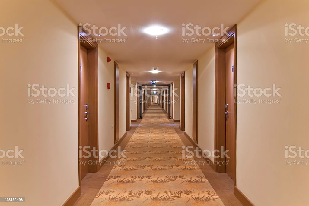 A long corridor with neutral walls and wooden doors stock photo