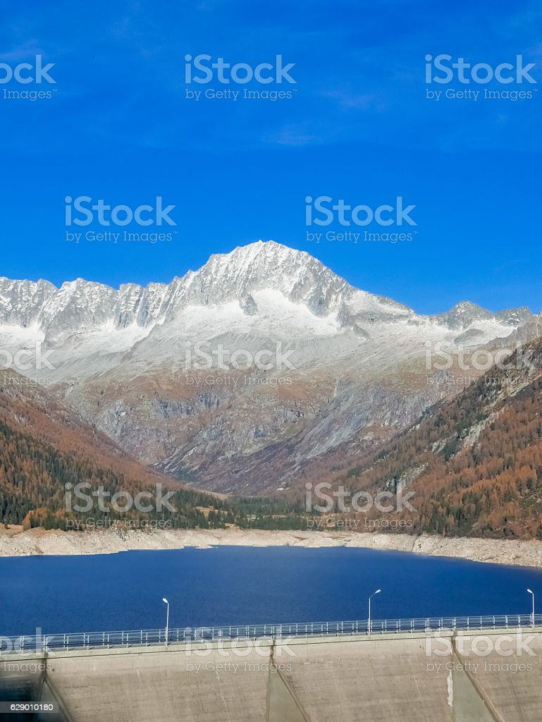 Long dam in the mountain valley in autumn during sunset stock photo