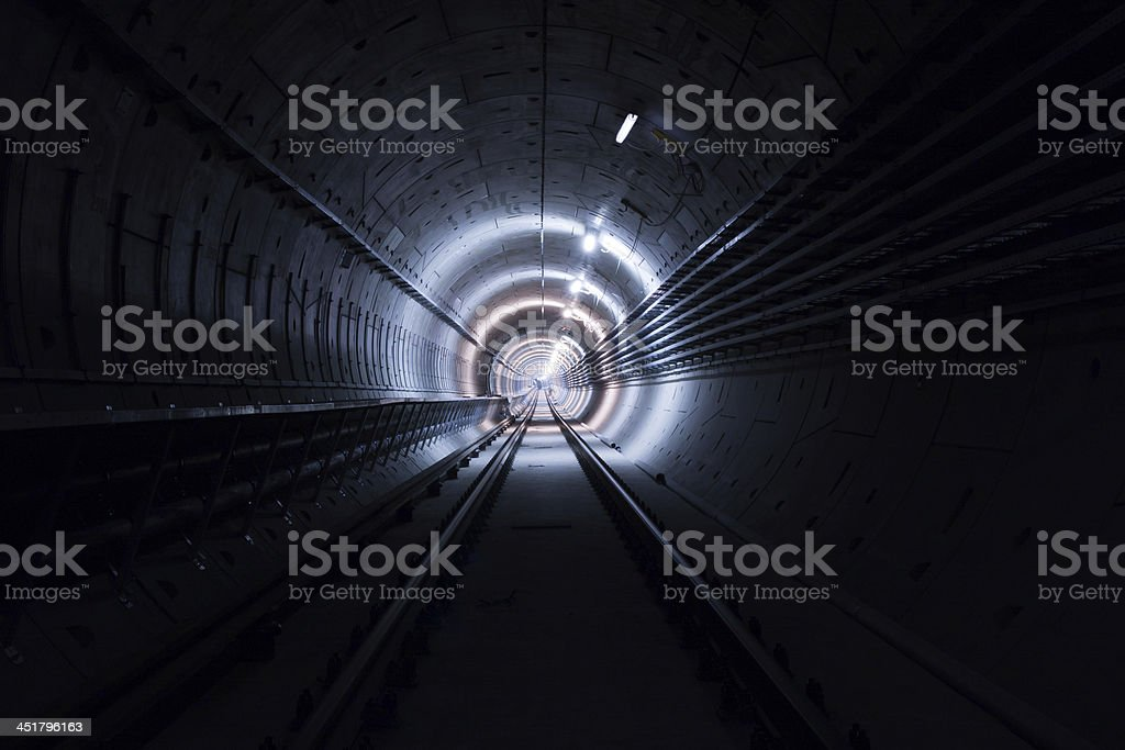 Long dark tunnel with tracks with a light at the end stock photo