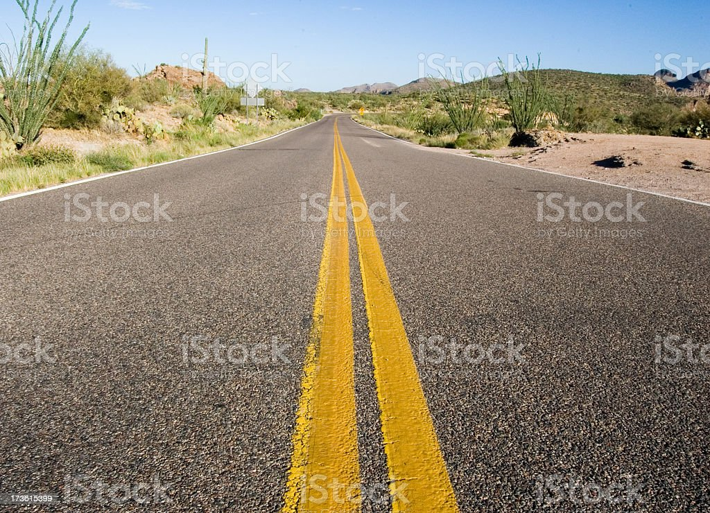 A long deserted desert road with a yellow separation line royalty-free stock photo