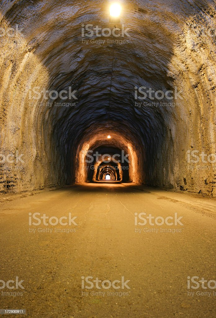 Long, dusty tunnel lit with overhead bulbs royalty-free stock photo