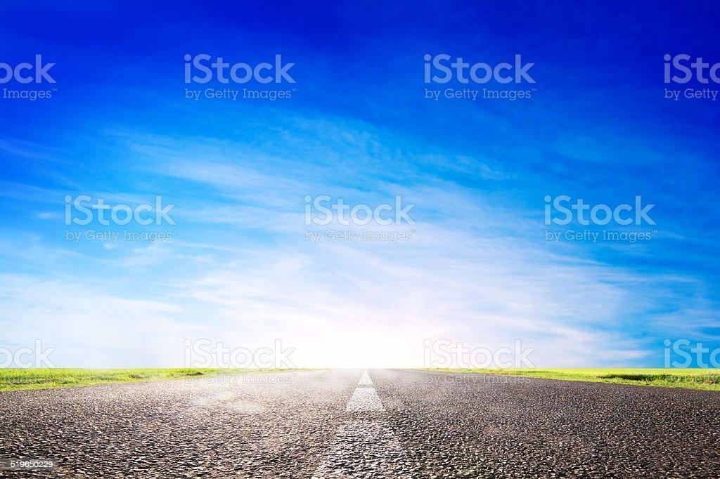 Long empty asphalt road, highway towards sun stock photo