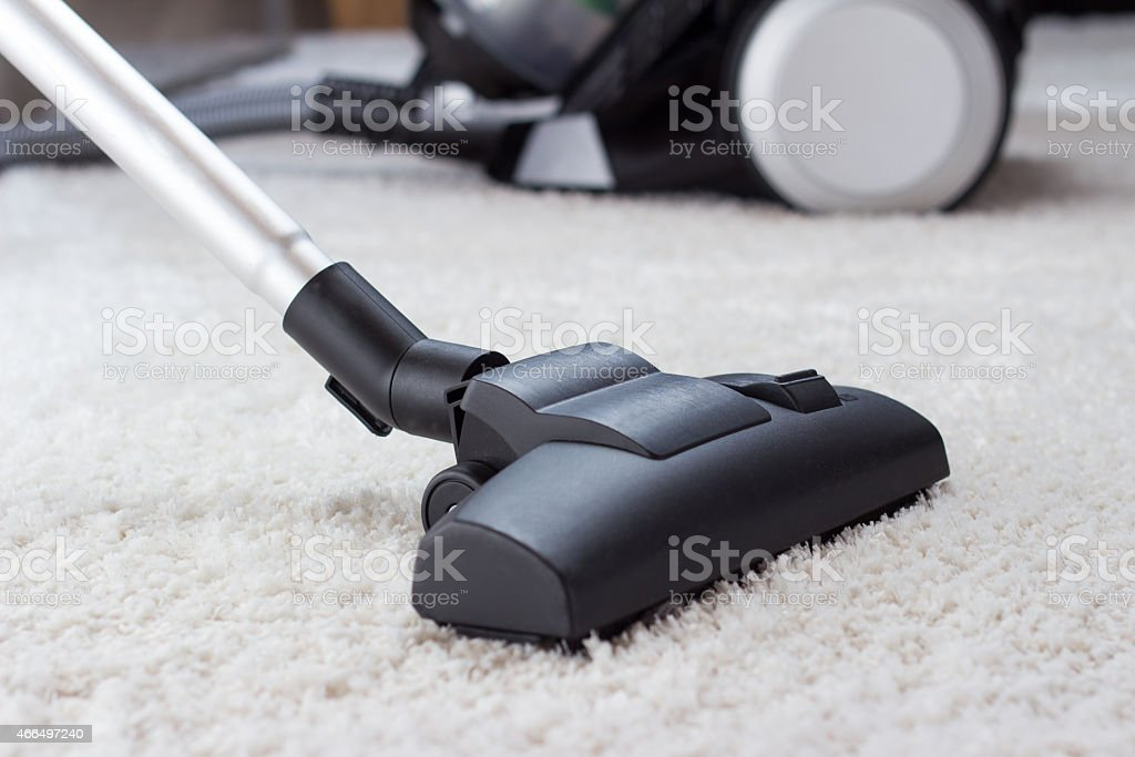 Long end of vacuum cleaner cleaning thick, white carpet stock photo