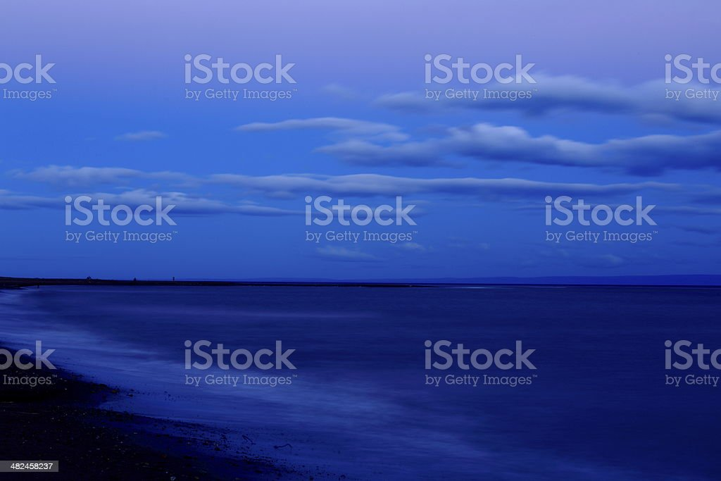 Long Exposure blurred Beach and cloudscape dramatic blue sky stock photo