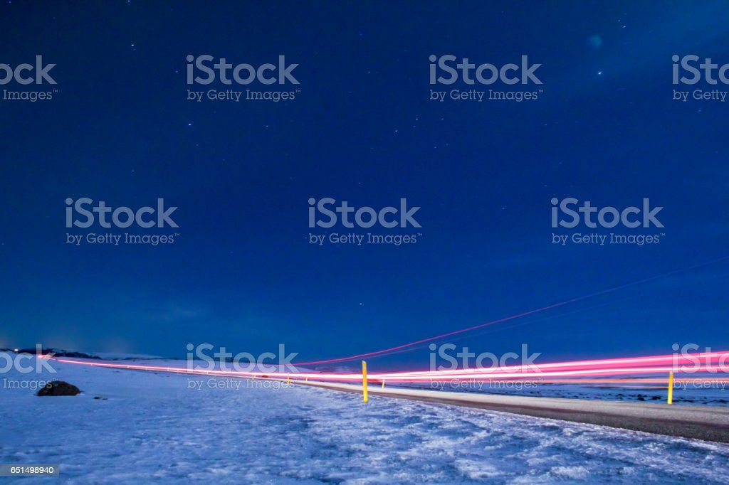 Long exposure car's light driving on highway surrounded by snow stock photo