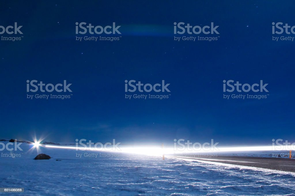 Long exposure car's light driving on road surrounded by snow stock photo